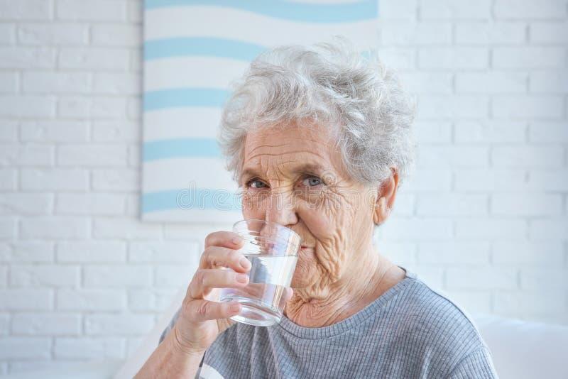 Äldre kvinnadricksvatten hemma arkivbild