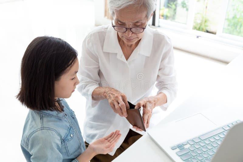Äldre kvinnahänder för Closeup öppen plånbok, farmor eller förmyndare som ger fickpengar till sondottern, asiatiskt begära för li royaltyfria foton