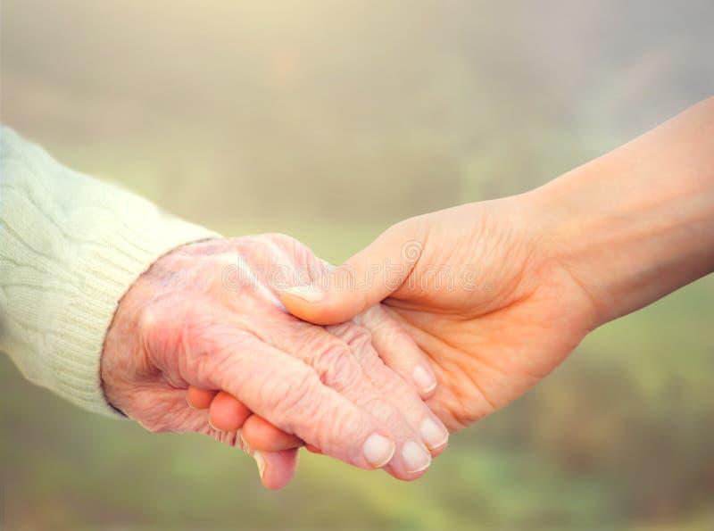 Äldre kvinnainnehavhänder med den unga anhörigvårdaren arkivbild