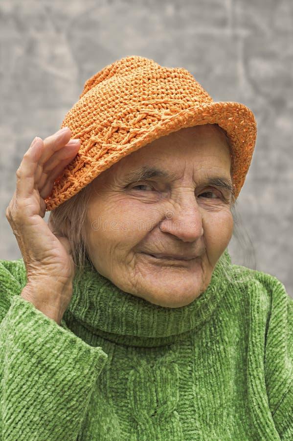 Äldre kvinnainnehavhand nästan ett öra royaltyfri foto