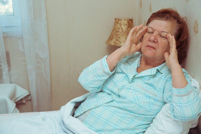 Äldre kvinnakänsla som är sjuk i säng arkivbild