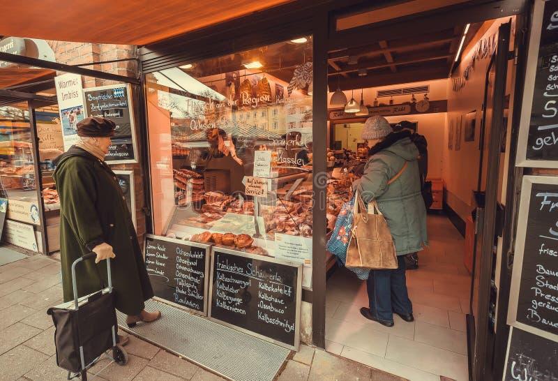 Äldre kvinnaköpandebacon och korv i ett köttlager på Viktualienmarkt arkivfoton