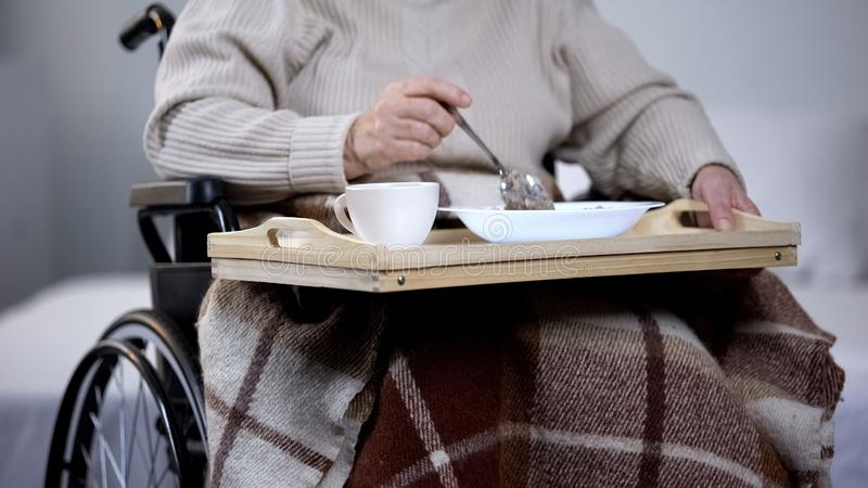 Äldre kvinnarullstol som äter matställen i vårdhemmet, sjukhusservice, mat royaltyfria foton