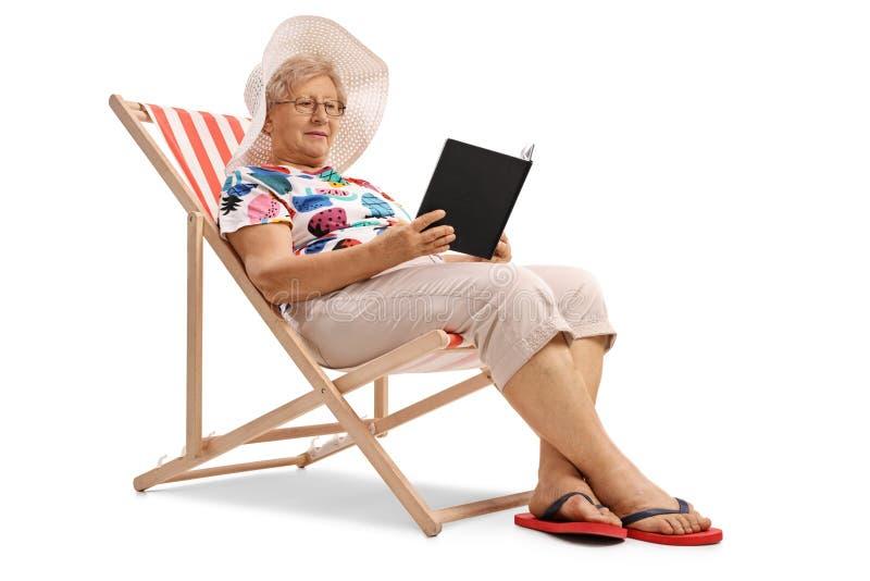 Äldre kvinnasammanträde i en solstol och en läsning en bok royaltyfria foton
