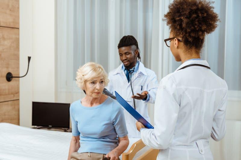 Äldre kvinnasammanträde på en sjukhussäng med två unga doktorer med skrivplatta- och röntgenstrålefotoanseende royaltyfria bilder