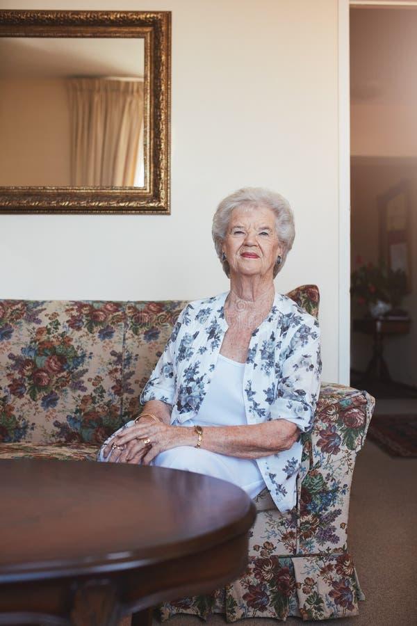 Äldre kvinnasammanträde på en soffa på gamlinghemmet royaltyfri fotografi