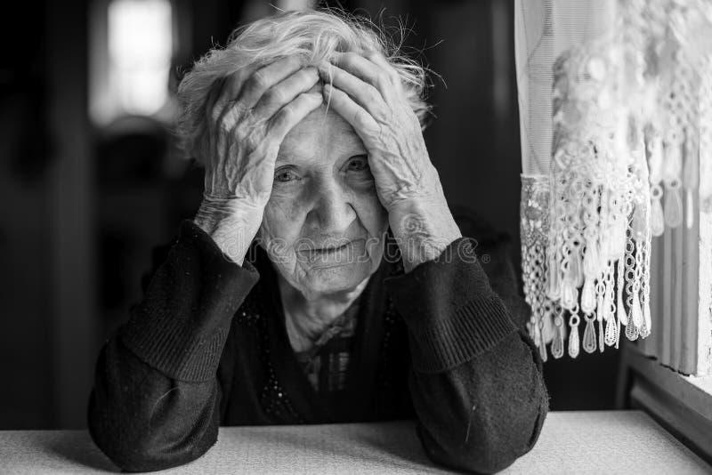 Äldre kvinnasammanträde på en tabell i ett deprimerat tillstånd royaltyfria foton