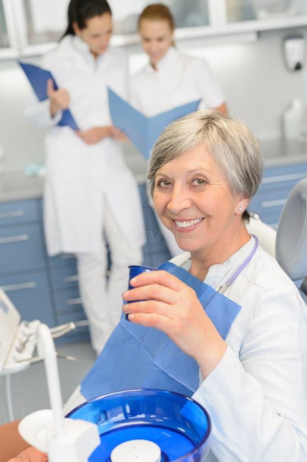 Äldre kvinnatandläkarelag på tand- kirurgi royaltyfria foton