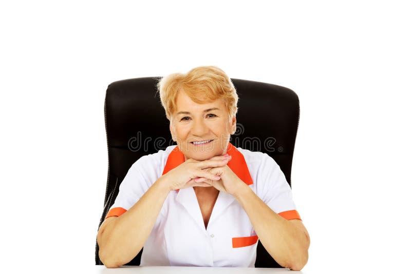 Äldre kvinnligt doktors- eller sjuksköterskasammanträde för leende bak skrivbordbenägenheten på händer arkivbild