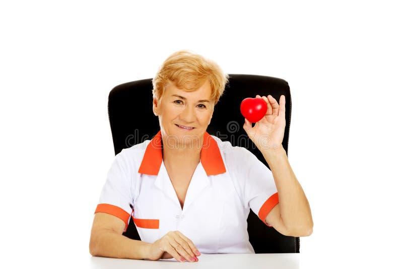 Äldre kvinnligt doktors- eller sjuksköterskasammanträde för leende bak skrivbordet och hållhjärtaleksaken royaltyfri foto