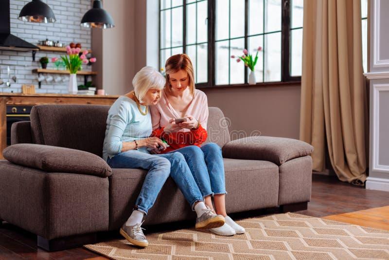 Äldre kvinnligt sammanträde på soffan med hennes barn-vuxen människa dotter royaltyfri foto