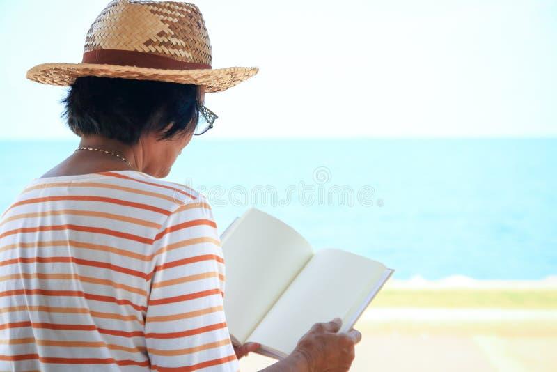 Äldre kvinnor öppnar för att läsa böcker royaltyfri bild