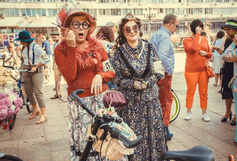 Äldre kvinnor i tappningklänningar som har gyckel under den Retro kryssningen för stadsfestival fotografering för bildbyråer