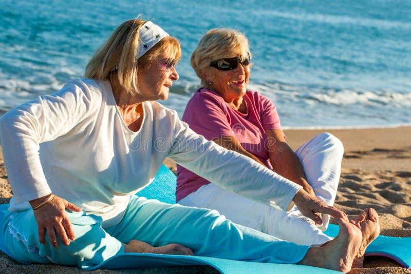 Äldre kvinnor som gör sträckning, övar på stranden. arkivbild