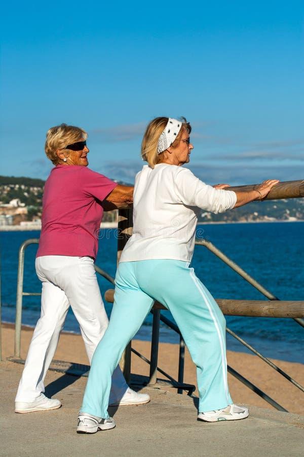 Äldre kvinnor som sträcker, innan att jogga. royaltyfri bild