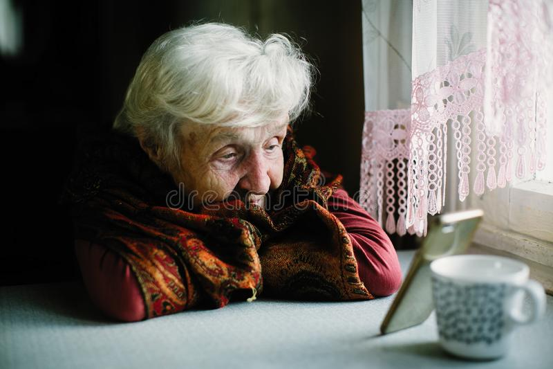 Äldre ledset kvinnasammanträde på tabellen som ser skärmen av smartphonen royaltyfri bild