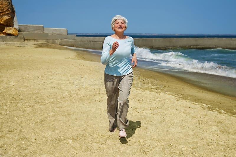 Äldre lycklig kvinnaspring på stranden längs kusten nära havet royaltyfria foton