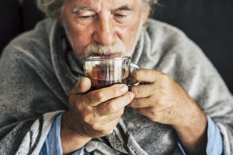 Äldre män med säsongsbunden höstsjukdom feber kalla problem att dricka ett apotek eller ett varmt te för att bli frisk - royaltyfri foto
