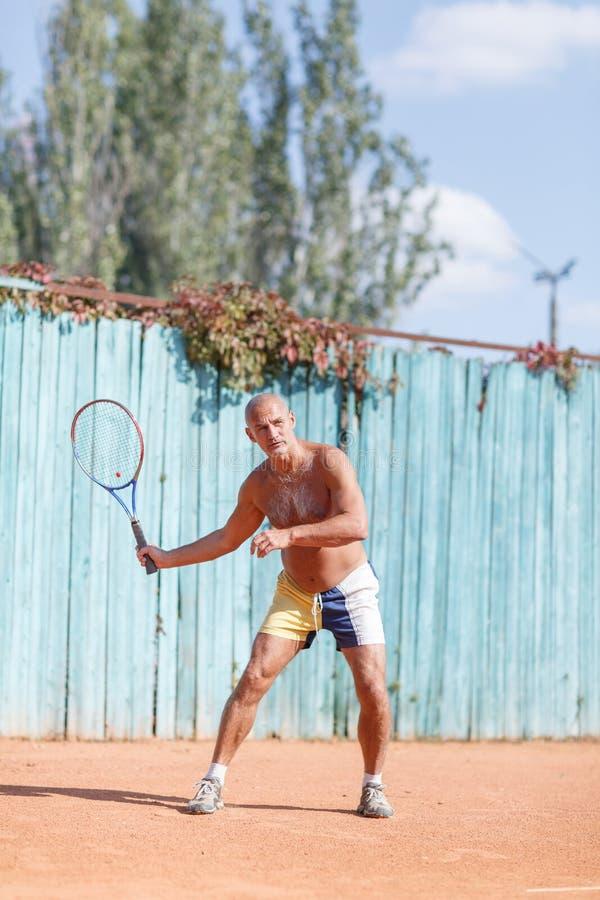 Äldre män slogg bollen på tennisbanan arkivfoton