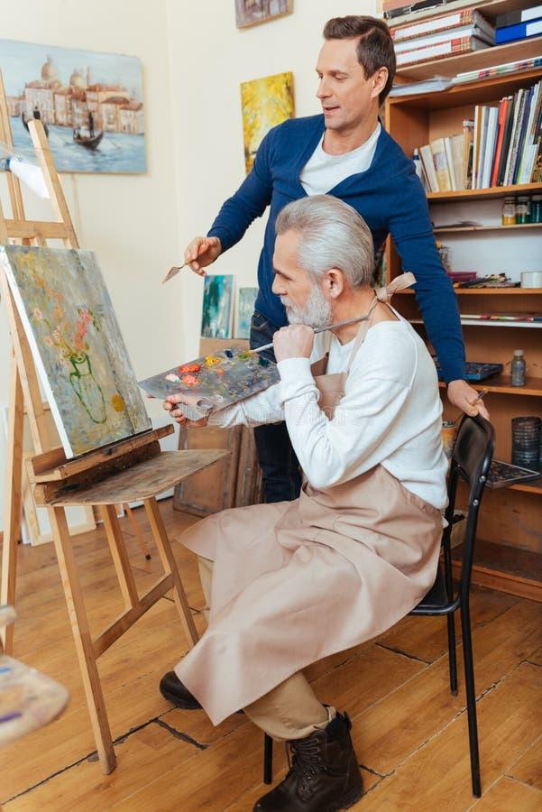 Äldre man för ambitiös konstnärportion i målning royaltyfria foton