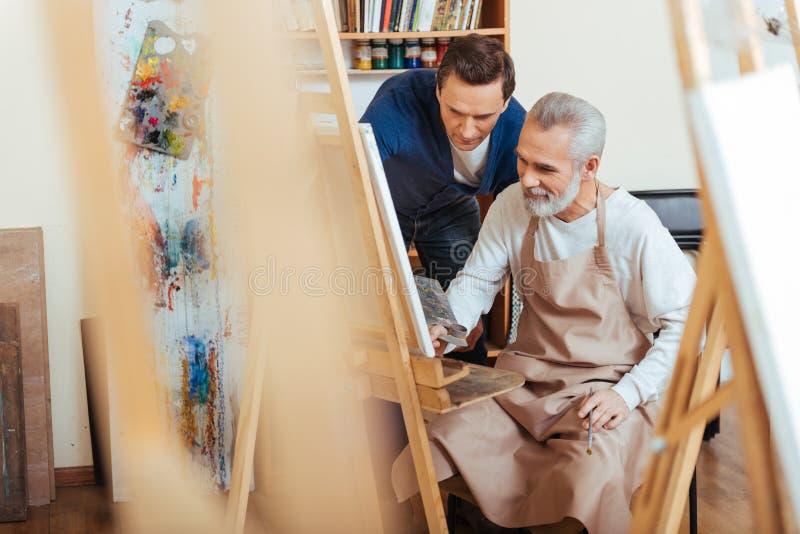 Äldre man för stilig konstnärportion i målning royaltyfri bild
