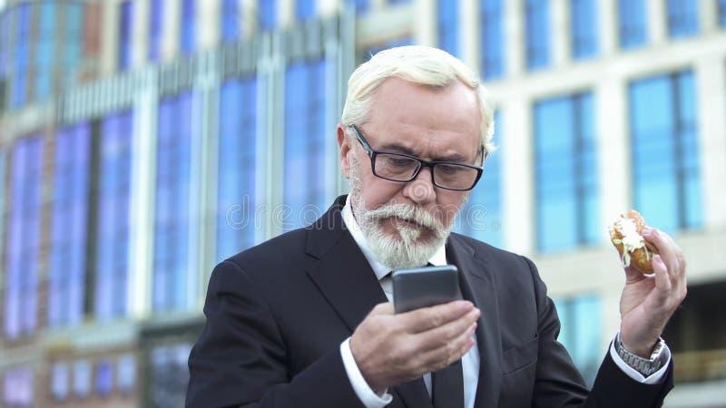 Äldre man i dräkt som äter hamburgaren som kontrollerar mejl, stressigt jobb, brist av tid arkivfoto
