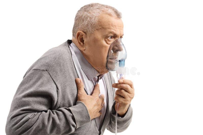 Äldre man med astma genom att använda en inhalator och rymma hans bröstkorg arkivfoton