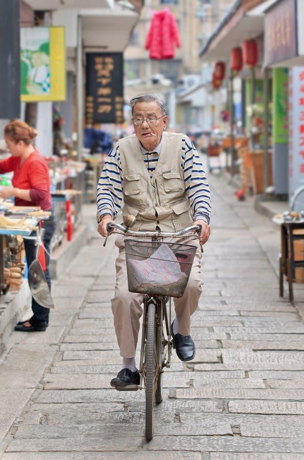 Äldre man med cigaretten på hans cykel, Yangzhou, Kina royaltyfria foton