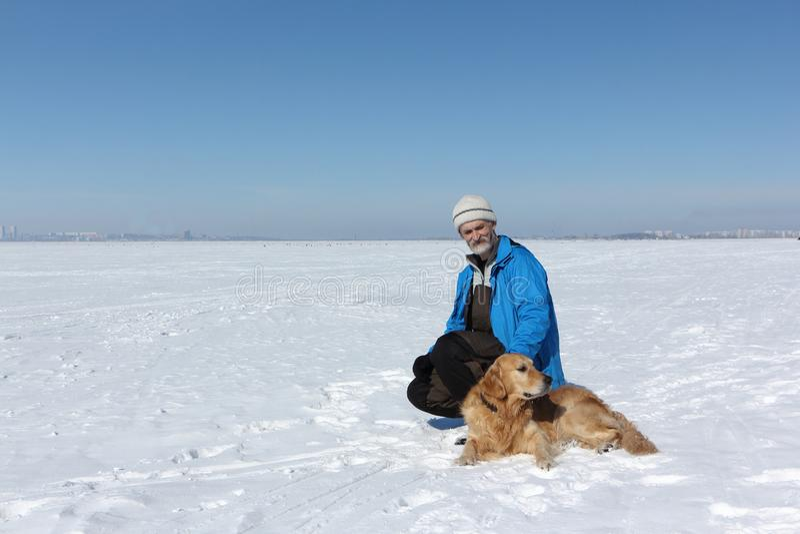 Äldre man med ett skägg i ett blått omslag och en hund en labradornolla arkivbilder