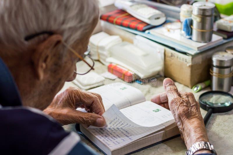 Äldre man med exponeringsglas som hemma läser handstilar i anteckningsbok nära fönstret arkivfoton