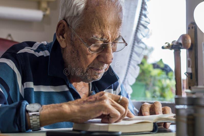 Äldre man med exponeringsglas som hemma läser handstilar i anteckningsbok nära fönstret arkivfoto