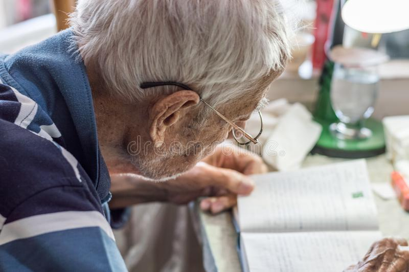 Äldre man med exponeringsglas som hemma läser handstilar i anteckningsbok nära fönstret royaltyfri bild