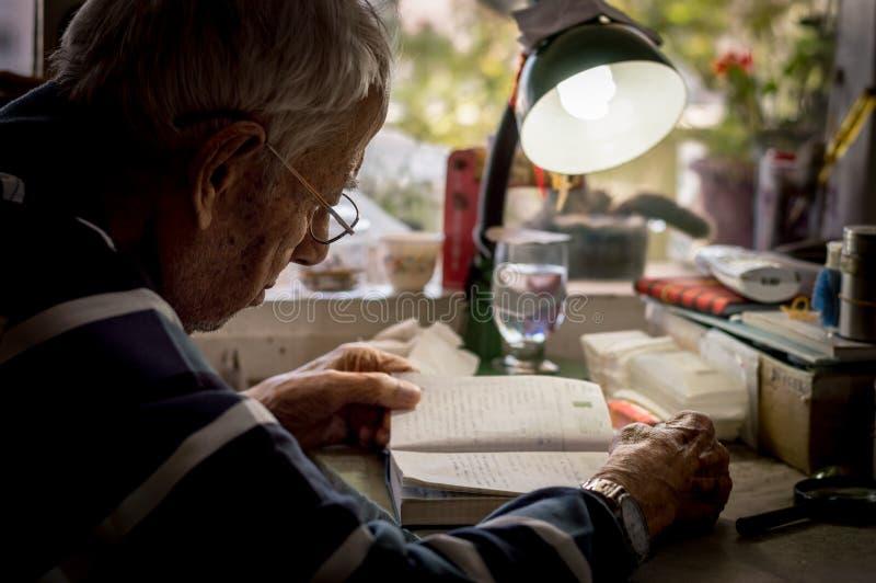 Äldre man med exponeringsglas som hemma läser handstilar i anteckningsbok nära fönstret royaltyfria foton