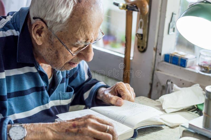 Äldre man med exponeringsglas som hemma läser handstilar i anteckningsbok nära fönstret arkivbilder