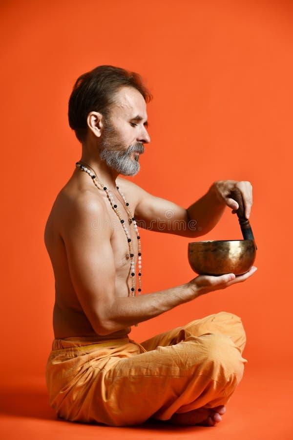 Äldre man med grå yogi för ett skägg i det bra fysiska forminnehavet som sjunger bunken royaltyfri bild