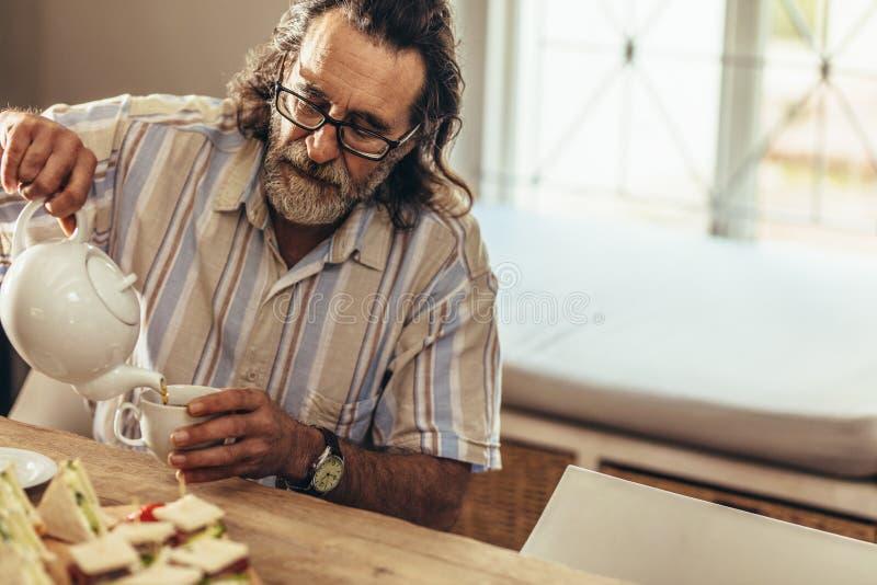 Äldre man med hällande te för skägg i kopp royaltyfria bilder