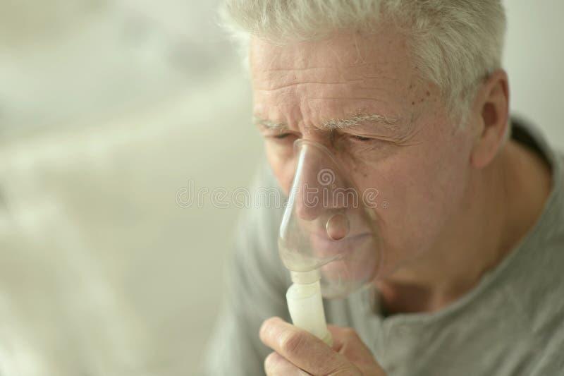 Äldre man med influensainandning royaltyfria bilder