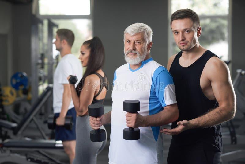 Äldre man och allvarlig idrottsman nen som ser kameran fotografering för bildbyråer