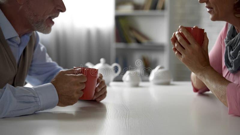 Äldre man och kvinna som sitter på köksbordet som dricker te, lyckliga par royaltyfri bild