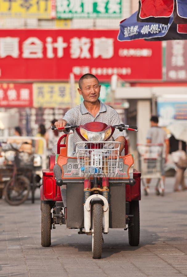 Äldre man på den elektriska cykeln, Peking, Kina royaltyfria foton
