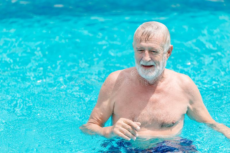 Äldre man simmade i poolen ensam semester royaltyfri bild