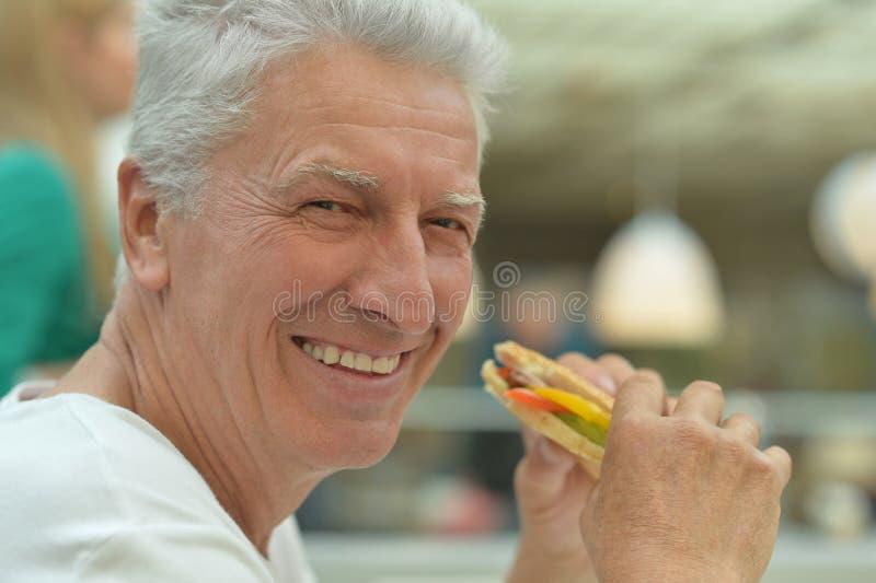 Äldre man som äter snabbmat fotografering för bildbyråer