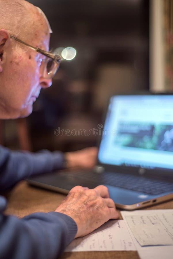 Äldre man som använder en dator för att kontrollera hans pengar direktanslutet, Hampshire, England, U K royaltyfri fotografi