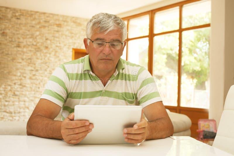 Äldre man som använder en elektronisk minnestavla arkivbild