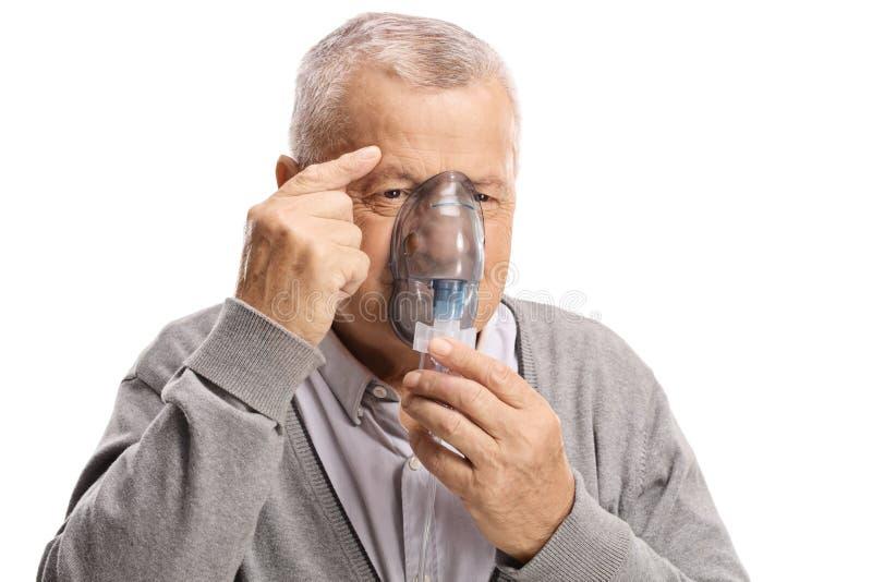 Äldre man som använder en inandningmaskering arkivfoto