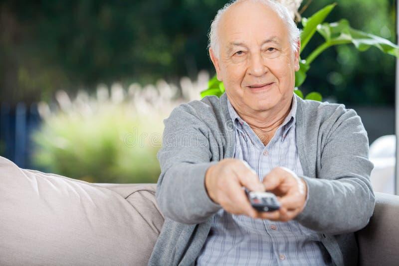 Äldre man som använder fjärrkontroll, medan sitta på arkivfoto