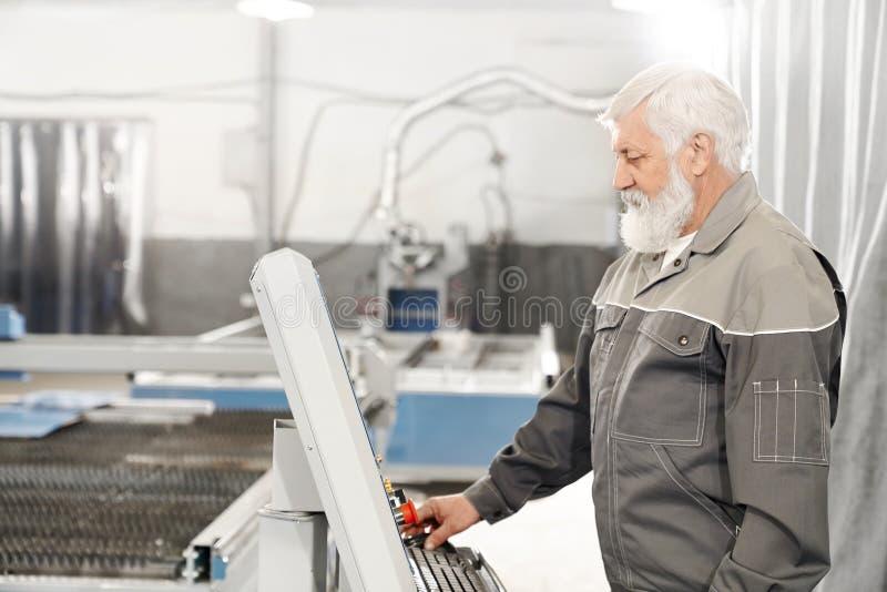 Äldre man som arbetar med laser-klippmaskinen på fabrik fotografering för bildbyråer