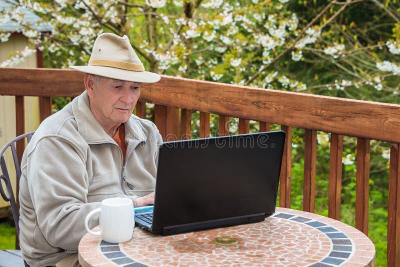 Äldre man som arbetar på bärbar datordatoren royaltyfria foton
