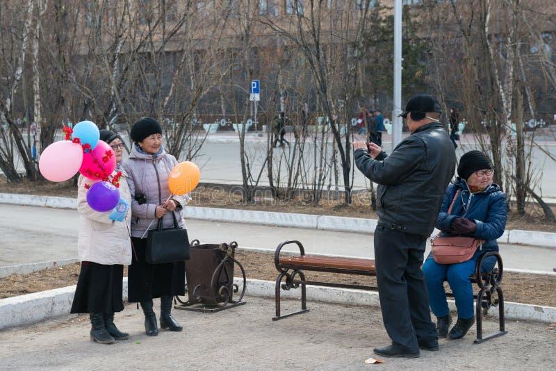 Äldre man som fotograferar två kvinnor som en minnessak av ferie för arbets- dag arkivfoton