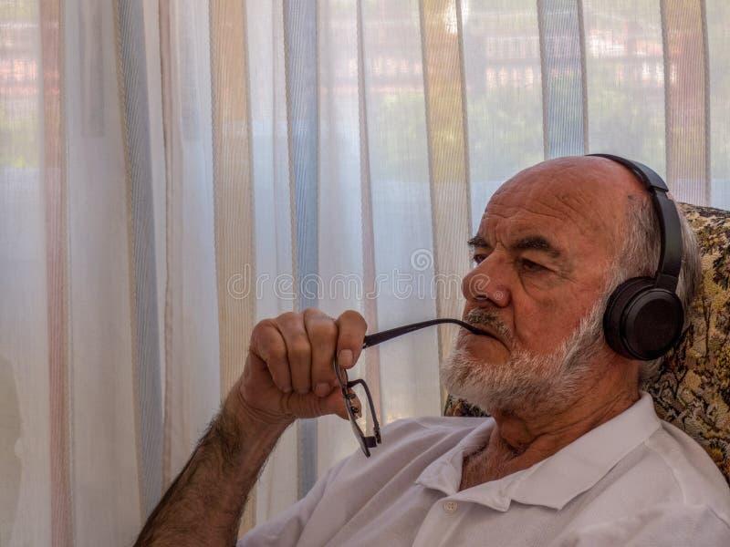 Äldre man som lyssnar till musik på trådlös hörlurar arkivfoton